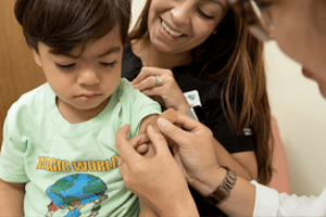 Young Boy Getting A Bandaid Put On His Shoulder By A Doctor