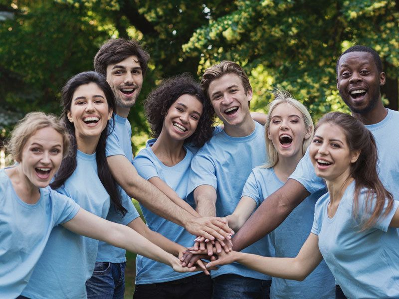 Group Of Young Adults Wearing Boy Shirts And Volunteering