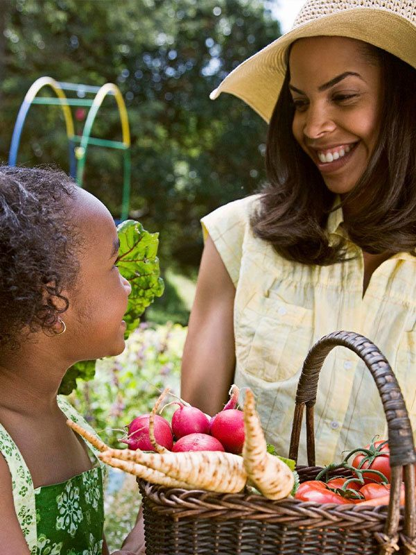 Mother and daughter getting vegetables from garden