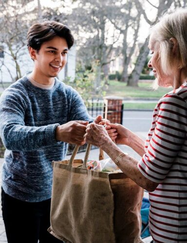 Young Guy Giving Groceries To An Elder Lady